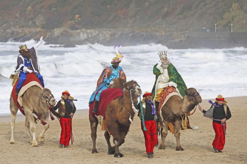 Los Reyes Magos a su llegada en camello a una playa del norte de España. EFE/Javier Etxezarreta