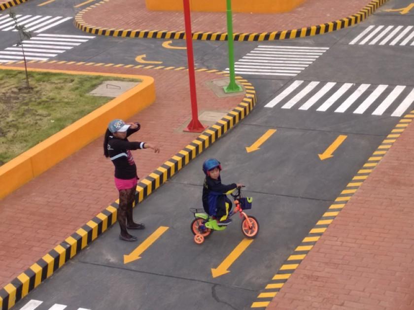 Una niña en bici, circulando por la autopista.