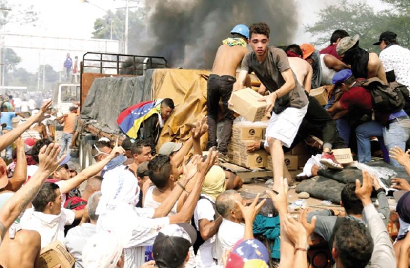 DESESPERACIÓN. Venezolanos intentan rescatar las cajas de ayuda humanitaria de camiones que terminaron en llamas.