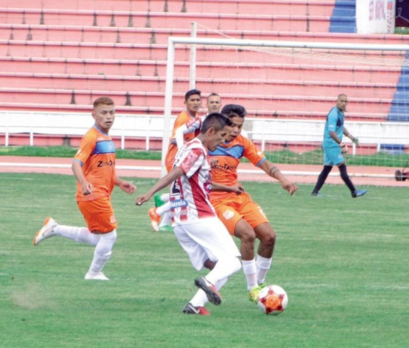 Lateral albirrojo Carlos Balcera intenta escapar ante la marca de un rival.