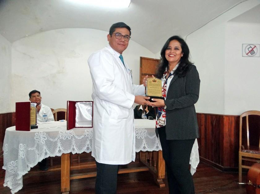 Enrique Leaño hace entrega del reconocimiento a Diana Duchén.