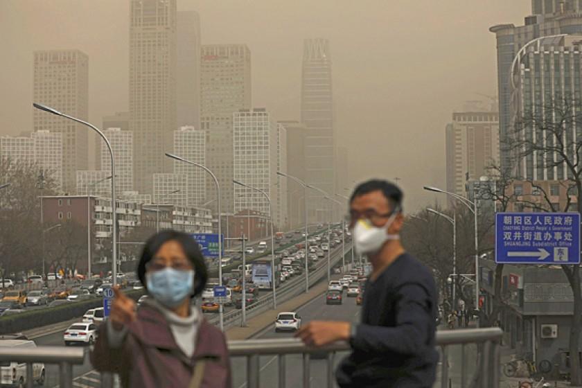 Pekín (China) Personas se cubren con tapabocas por la neblina que cubre la ciudad de Pekín (China)
