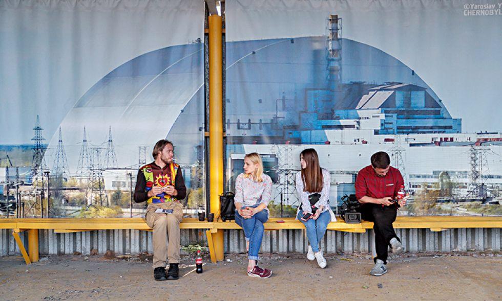Los visitantes esperan en una parada de autobús con un cartel gigante al fondo que representa el nuevo refugio protector sobre los restos del reactor nuclear Unidad 4 de la central