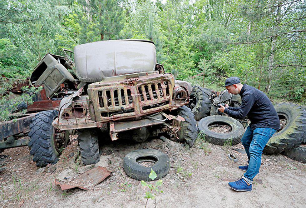 Un visitante toma una foto de un autobús abandonado durante una gira en Chernóbil (Ucrania), el 7 de junio de 2019. EPA/Sergey Dolzhenko