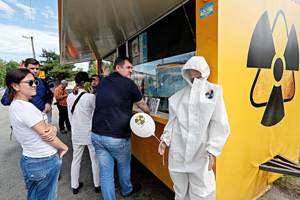 07/06/2019.- Los visitantes hacen cola en una tienda de recuerdos en el puesto de control de Dytyatky de la zona de Chernóbil (Ucrania). EFE/EPA/Sergey Dolzhenko