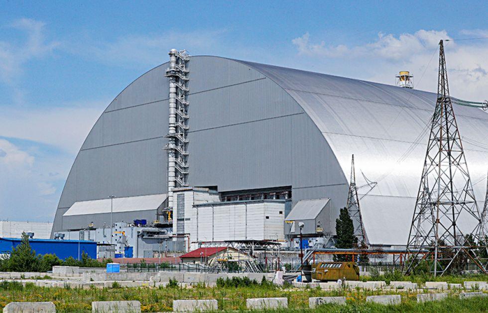 Chernóbil (Ucrania), 07/06/2019.- El nuevo refugio protector sobre los restos del reactor nuclear Unidad 4 de la central nuclear de Chernóbil, es visto a través de una ventana de u