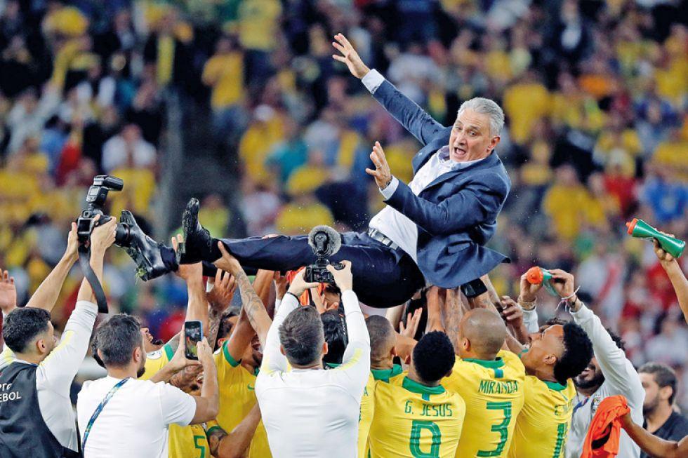 El entrenador de Brasil, Tite, es levantado por sus jugadores.