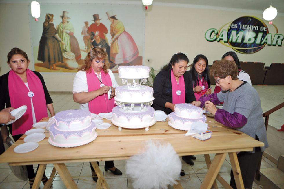 Las socias preparan la torta de aniversario.