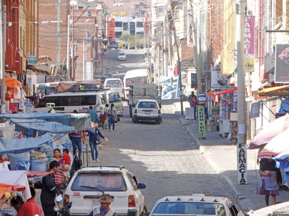 VÍA. Vista de la calle Jesús Lara donde se puede observar los puestos de papa, autos estacionados y el paso de los vehículos.