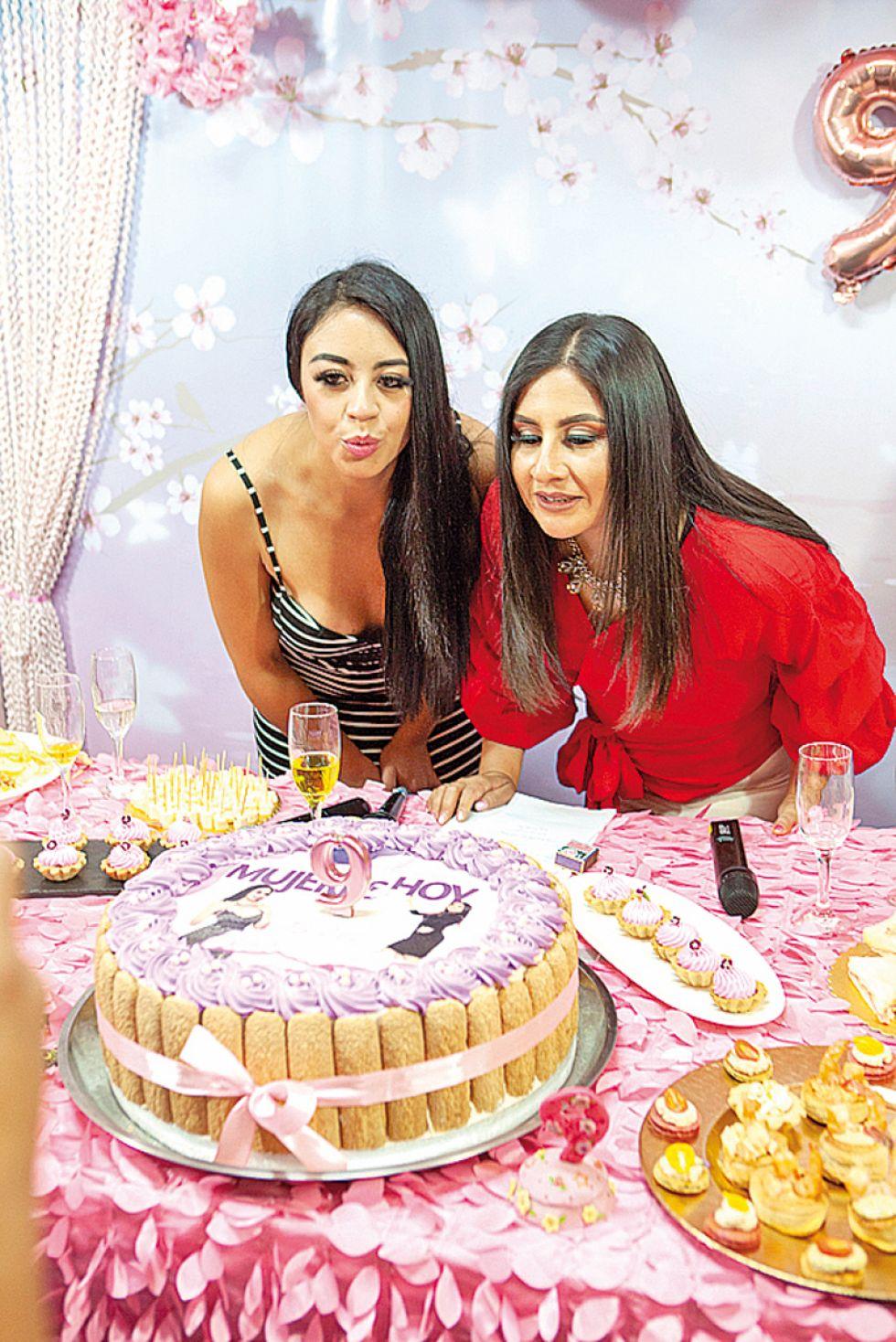 Nicole Gantier y Helga Flores apagan  la vela de aniversario.