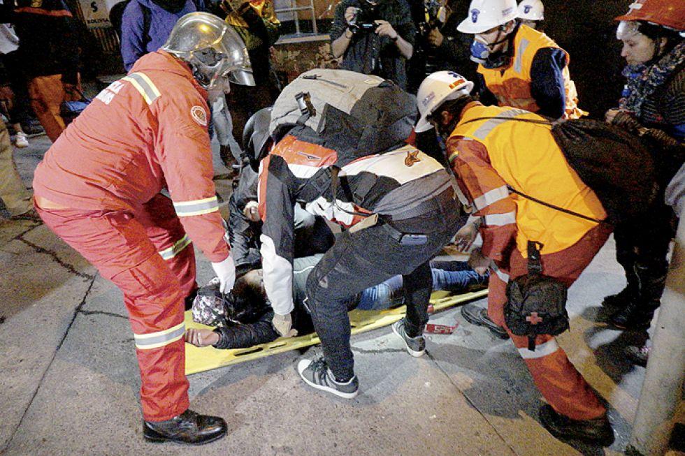 HECHO. Uno de los manifestantes es auxiliado por paramédicos tras ser herido en la refriega.