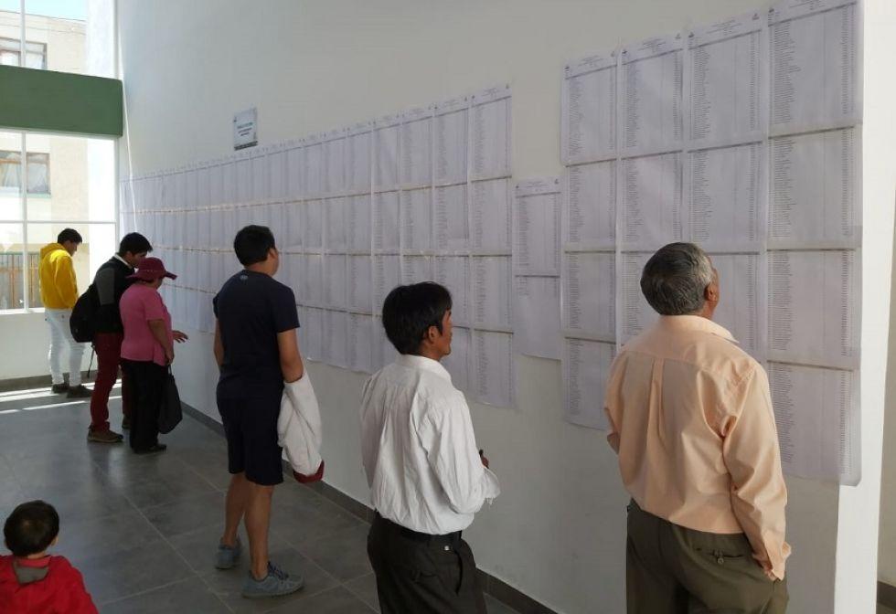 Electores buscando el número de mesa para emitir su voto.